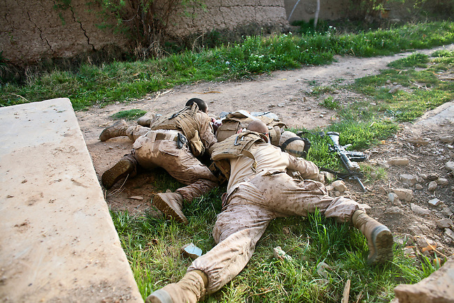 As gunfire cracks around them, Navy Corpsman Jonathan Duhart and a Marine protect Lance Cpl. Matthew W. McElhinney who has been hit in the back by a Taliban bullet at an abandoned school near Marjah, Afghanistan. March 10, 2010. DREW BROWN/STARS AND STRIPES