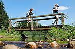 Bethlehem, CT- 03 July 2015-070315CM05-  Phil Musella holding daughter Ava, 2, and his wife, Amy of Monroe, walk over a bridge after picking cherries at March Farms in Bethlehem on Friday.  Families went to the farms to pick blueberries and cherries, two fruits currently in season.  For current picking conditions you can call the farm at (203) 266-7721. Christopher Massa Republican-American