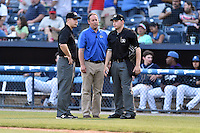 Asheville Tourists general manager Larry Hawkins, first base umpire Matt Carlyon and home plate umpire Ryan Powers discuss the light situation between innings of a game against the Hagerstown Suns at McCormick Field on April 28, 2016 in Asheville, North Carolina. The Tourists were leading the Suns 6-5 when the game was delayed in the top of the 6th inning due to darkness. (Tony Farlow/Four Seam Images)
