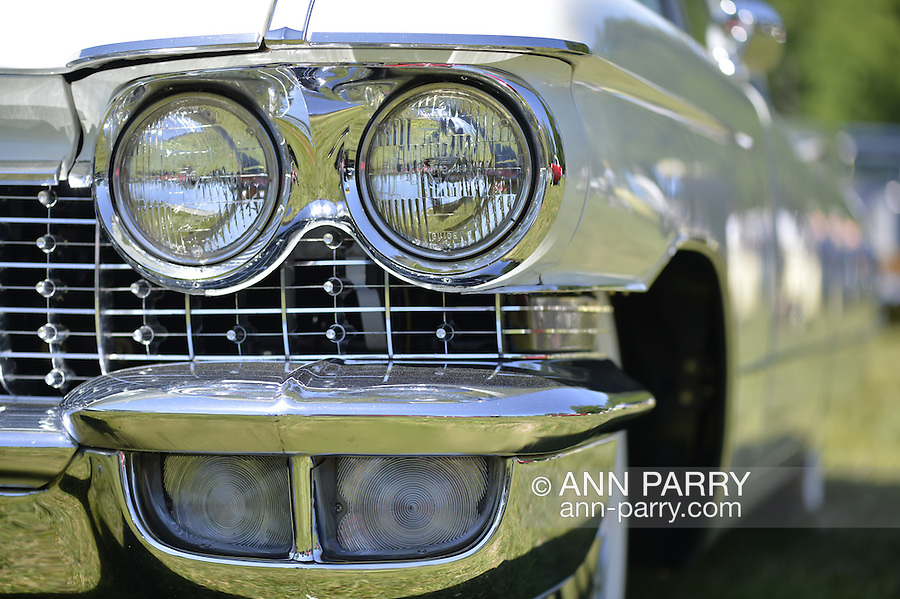 Westbury, New York, USA. June 12, 2016.  Chrome double headlights and running lights are seen in close up of classic1960 white Cadillac sedan on display at the Antique and Collectible Auto Show at the 50th Annual Spring Meet at Old Westbury Gardens, in the Gold Coast of Long Island, and sponsored by Greater New York Region, GNYR, Antique Automobile Club of America, AACA. Participating vehicles in the judged show included hundreds of domestic and foreign, antique, classic, collectible, and modern cars.