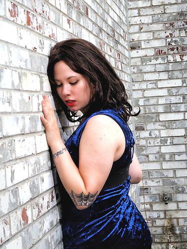 Model Pressed Against Whitewash Brick Wall