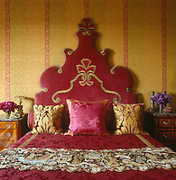 The master bed has a Venetian-inspired red velvet headboard and a damask cover
