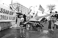 Mesa, Arizona. Febriary 23, 2012 - As Republican candidates debated in the Mesa Arts Center, protesters including undocumented students, tea partiers, occupy movement members and Syrian president opponents, shouted slogans and held up signs and placards outside. In this photograph, a small boy who was part of an Arizona-based group opposing Syrian president Bashar al-Assad politics waves a Syrian flag outside the Presidential Republican debate. Photo by Eduardo Barraza © 2012