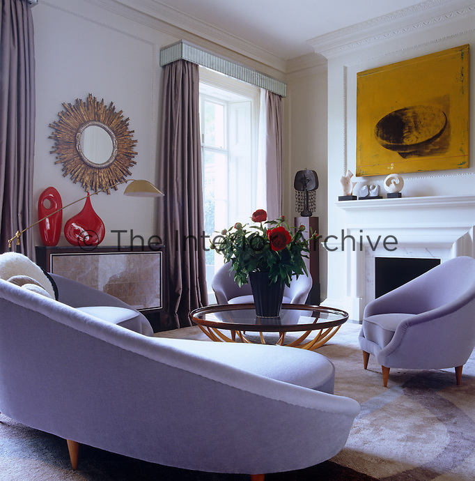 A deep yellow painting creates a vibrant note in counterpoint to the predominantly violet palette in this modern living room