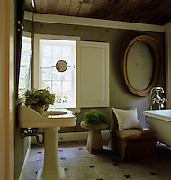 An empty antique oval picture frame hangs on the wall of this bathroom