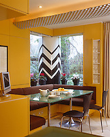 The kitchen/dining area consists of a contemporary banquette around a glass-topped table with a black and white zig-zag sculptural column in the garden beyond the window