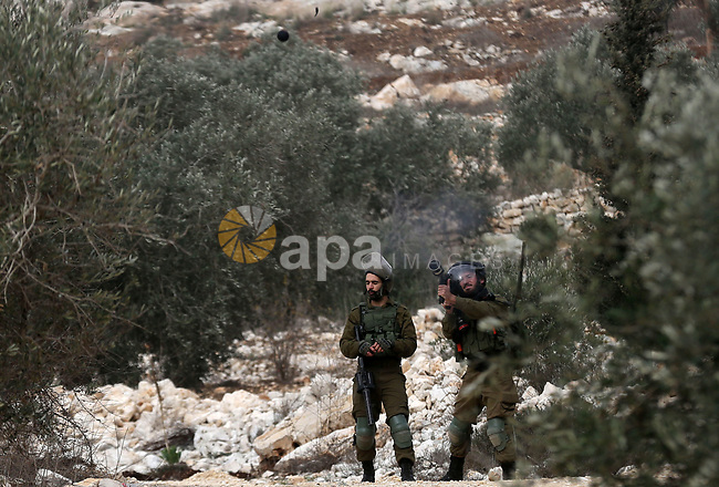 Israeli security forces take position during clashes with Palestinian protesters following a weekly demonstration against the expropriation of Palestinian land by Israel in the village of Kfar Qaddum, near the West Bank city of Nablus on December 13, 2019. Photo by Shadi Jarar'ah