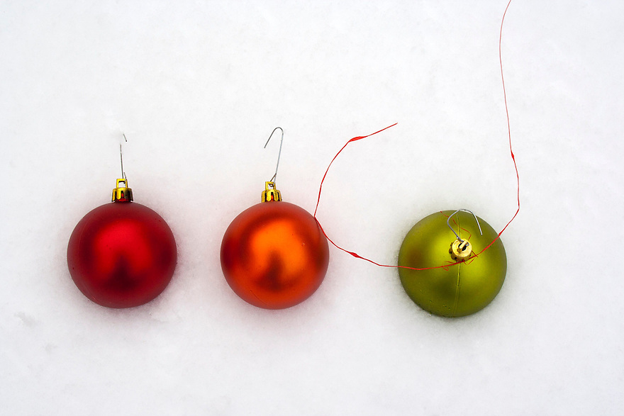 red orange and green christmas ornament in fresh snow