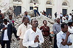 People stand on top of the rubble of the destroyed national cathedral for a church service on July 11, 2010 in Port-au-Prince, Haiti.