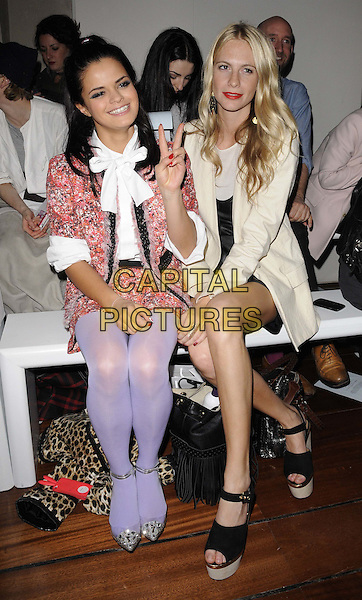 Bip Ling & Poppy Delevigne.attended the Antipodium autumn/winter 2012 salon show, London Fashion Week Day 2, BFC Gallery, Somerset House, The Strand, London, England, UK, 18th February 2012..LFW full length sitting front row  purple lilac tights cream coat black sandals  red skirt white pussybow shirt .CAP/CAN.©Can Nguyen/Capital Pictures.