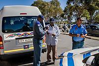 Die Polizisten Themba Runeli (li) und Enrico Pillay in Kapstadt, Südafrika, bei der Beschlagnahmung eines Minibusses, der auf einer nicht genehmigten Strecke gefahren war.