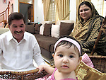 4 November 2012, Karachi, Pakistan.   Former Deputy Superintendant of Quetta police Shaban Ali (white kurta) with his wife Hamida  and grand daughter Sukhina in their home in Karachi, the Pakistani port city they fled to after a suicide bomb attack on his car in 2011. Picture by Amanda Hodge/The Australian Magazine..