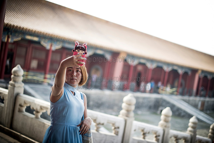 A Chinese woman takes a selfie on the pavillion of the Forbidden City in Beijing, China, July 20, 2014.<br /> <br /> Smartphones are an essential tool of Chinese ordinary life. Everywhere in China, people use them to take pictures to share online, to talk and chat, to play videogames, to get access to the mainstream information, to get connected one each other. In the country where the main global social media are forbidden - Facebook, Twitter and Youtube are not available  -, local social networks such as WeChat have a wide spread all over the citizens. The effect is an ordinary and apparently compulsive way to get easy access to digital technology and modern way of communication. <br /> A life through the display. Yes, We Chat.<br /> <br /> © Giorgio Perottino