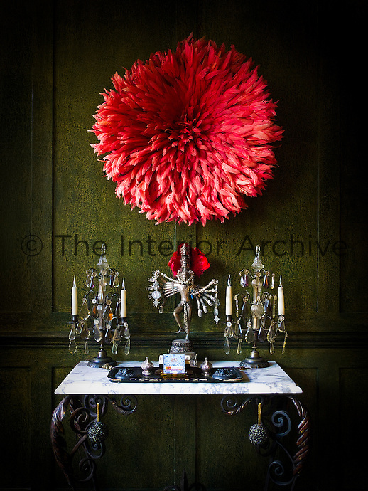 An eclectic combination of objects including a pair of crystal candelabra and an Ethiopian headdress against a painted wood-panelled wall in the living room