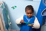 Educaton preschool 4-5 year olds art activity painting girl in smock pausing from painting to cover her own hand in green paint horizontal