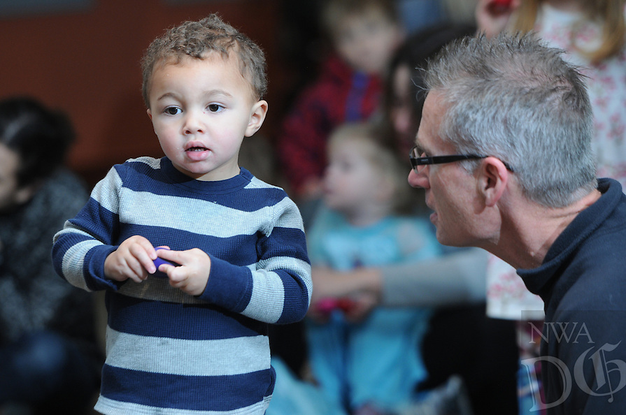 NWA Media/ J.T. Wampler - Greg Scharlau of Fayetteville, right, and his grandson Kaiden Wood, 2, listen to a live performance Saturday Dec. 27, 2014 at the Fayetteville Public Library. Jeremy Babcock of Chicago and the band Dreamtree Shakers performed a free show for the children.