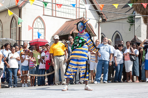 Traditional Mas parade - jab jab performs with crowd watching