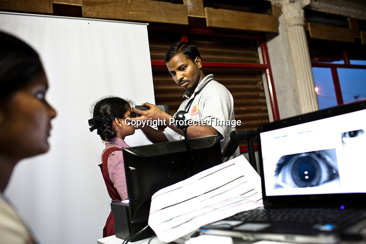 An official assists a young girl to get her iris scanned as part of the enrollment that is on its way in Naagaaram village, outskirts of Hyderabad in Andhra Pradesh, India. India is assigning each one of its 1.2 billion people a unique ID number based on digital finger prints and iris scan. Photograph: Sanjit Das/Panos