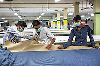 Workers preparing layers of cloth to be cut into shapes for sewing into clothing at the Pratibha vertically integrated garment unit in Indore, Madhya Pradesh, India on 11 November 2014. Photo by Suzanne Lee for Fairtrade