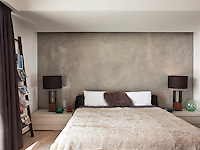 The master bedroom has a contemporary and masculine feel with a polished concrete wall and black, brown and neutral colour palette