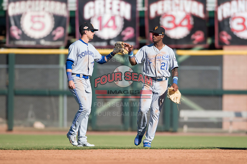 Surprise Saguaros right fielder Nick Heath (21), of the Kansas City Royals organization, celebrates a victory with Cavan Biggio (26), of the Toronto Blue Jays organization, after an Arizona Fall League game against the Scottsdale Scorpions at Scottsdale Stadium on October 26, 2018 in Scottsdale, Arizona. Surprise defeated Scottsdale 3-1. (Zachary Lucy/Four Seam Images)