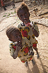 Two girls in the pottery village of Kalabougou near Segou, Mali sip frozen drinks from plastic blags.