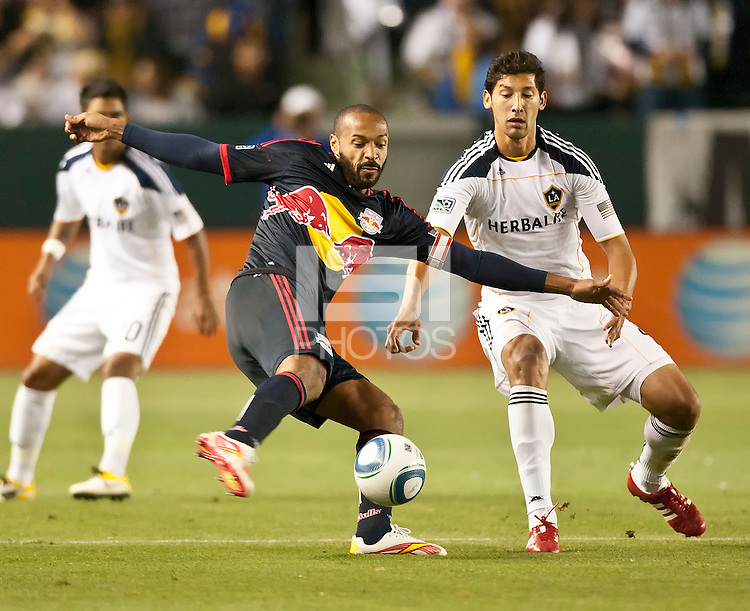 CARSON, CA – May 7, 2011: New York Red Bull forward Thierry Henry (14) attempts to pass the ball past LA Galaxy defender Omar Gonzalez (4) during the match between LA Galaxy and New York Red Bull at the Home Depot Center, May 7, 2011 in Carson, California. Final score LA Galaxy 1, New York Red Bull 1.