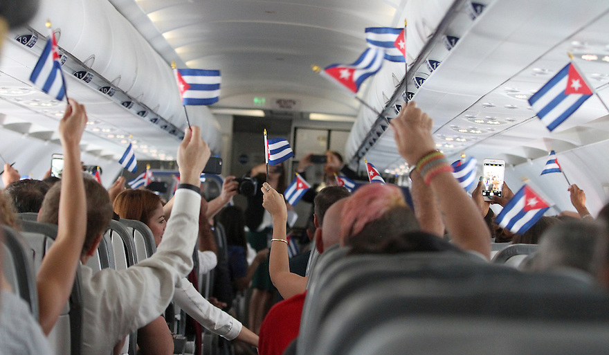 Shortly after take-off from Fort Lauderdale airport customers are seen waving Cuban flags while onboard JetBlue's inaugural commercial flight to Cuba on Wednesday, Aug. 31, 2016 (Donald Traill/AP Images for JetBlue)