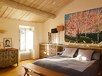 A large painting of a cherry tree hangs behind the bed in this simple contemporary bedroom