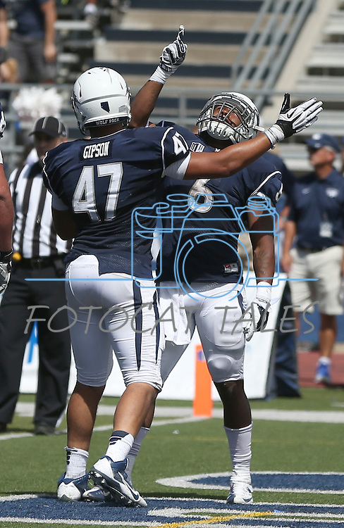 Nevada's Don Jackson (6) celebrates with teammate Jarred Gipson (47) after scoring a touchdown against Southern Utah during the second half of an NCAA college football game on Saturday, Aug. 30, 2014, in Reno, Nev. (AP Photo/Cathleen Allison)