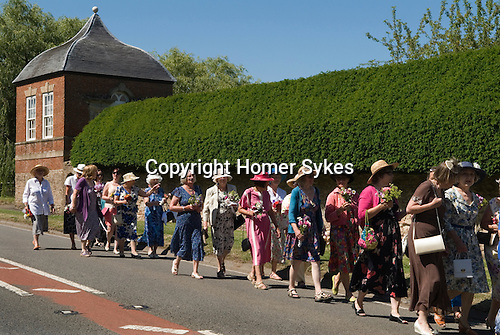 "Stowey Female Friendly Society ( The Womens Walk ) Club Day. Local women and flower girls walk from the village to the grave of Tom Poole ) founder 1806) at St Marys Church. Dress code ""formal, with hat and posy of flowers."" Nether Stowey Somerset 2014."