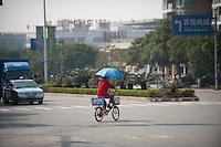 A Woman Riding A Bicycle With An Umbrella in Dongguan, China.  © LAN