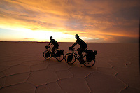 Brook Allen and Gregg Bleakney cycle over the Salar de Uyuni at Sunset - Bolivia - South America