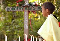 Criança acende vela no túmulo de irmã Dorothy Stang durante a cerimônia pelos seis meses de sua morte. Em segundo plano padre Amaro.<br />Anapú, Pará, Brasil<br />Foto Paulo Santos/Interfoto<br />12/08/2005