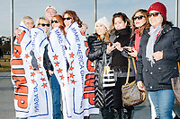 People pose for pictures draped in Trump flags next to the Washington Monument in Washington, DC, on Jan. 19, 2017, the day before the inauguration of president-elect Donald Trump.