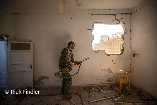 August 2017. Raqqa, Syria.<br /> Foreign volunteer fighter 'Macer Gifford', aged 30 and originally from Cambridgeshire, walks through an abandoned house as he tries to locate a spot to fire his sniper rifle toward ISIS positions.<br /> The MFS (Syriac Military Council) are a group of Assyrian Christians who fight alongside the Syrian Democratic Forces in the fight to topple ISIS.<br /> Photographer: Rick Findler