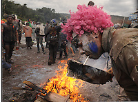 Feb. 27, 2011 - Galaxidi, Greece: Man with painted face and pink wig lights his cigarette with a piece of wood taken from the street fire. Revellers participate in a flour war to celebrate 'clean Monday', a day that marks the end of the carnival season and the start of the 40-day Lent period of the Orthodox Easter (Foto Insidefoto / Maro Kouri / Anatomica Press) .A Galaxidi, in Grecia, si è svolta la battaglia della farina, Clean Monday o Pure Monday, che segna la fine del carnevale..ITALY ONLY