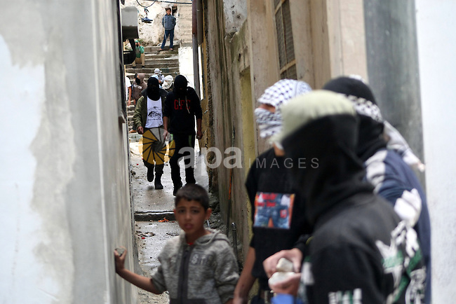 """Palestinian masked protesters stand take part in clashes with Israeli soldiers after a rally marking the Nakba or the """"Day of Catastrophe"""" in al-Aroub refugee camp in the West Bank city of Hebron, on May 15, 2013. Nakba Day is the annual day of commemoration of the displacement of Palestinians after the establishment of the state of Israel in 1948. Photo by Mamoun Wazwaz"""