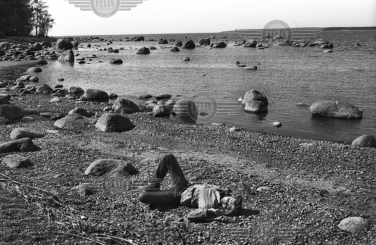 A man lies on the sand on a beach on the Gulf of Finland.