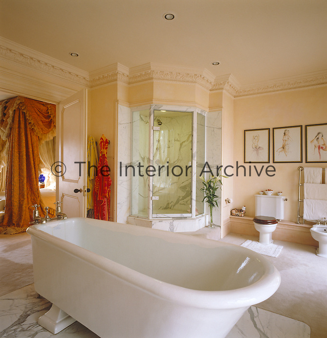 This 1920s roll-top bath dominates the peach coloured bathroom which also benefits from a large marble corner shower