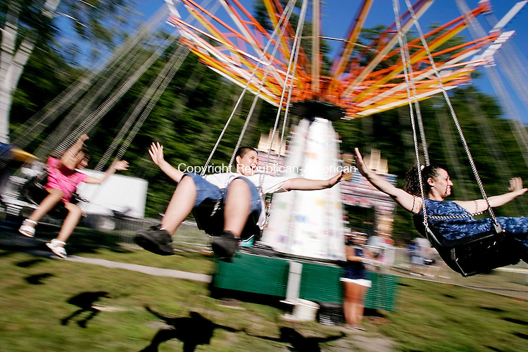 WATERBURY, CT -- 05 August 2007 -- 080507TJ18 - Joshua Merly, 12, from Fairfield, Conn., shares a swing ride with his mother, Jennifer  Brevard, left, and sister Lynnaija Brevard, 5, at the Pontelandolfo Club's 21st annual 2007 Festa di San Donato in Waterbury on Sunday, August 5, 2007. T.J. Kirkpatrick/Republican-American