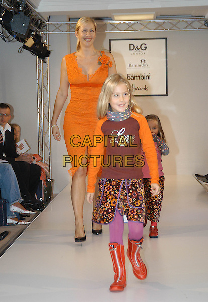 """TANIA BRYER.As part of Made In Italy (6th September to the 30th October) at Harrods, celebrity mum hosts a dazzling D&G (Dolce & Gabbana) childrenÕs fashion show in association with """"Vogue Bambini"""" and BarnardoÕs at Harrods, Knightsbridge, London, October 1st 2004..full length orange dress children daughters catwalk.Ref: HT.www.capitalpictures.com.sales@capitalpictures.com.©Capital Pictures."""