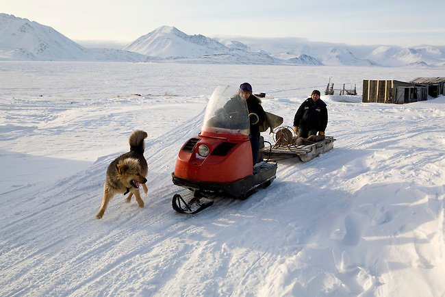 Yupik Eskimo hunters travelling by snowmobile in New Chaplino village. Chukotskiy Peninsula, Chukotka, Siberia, Russia