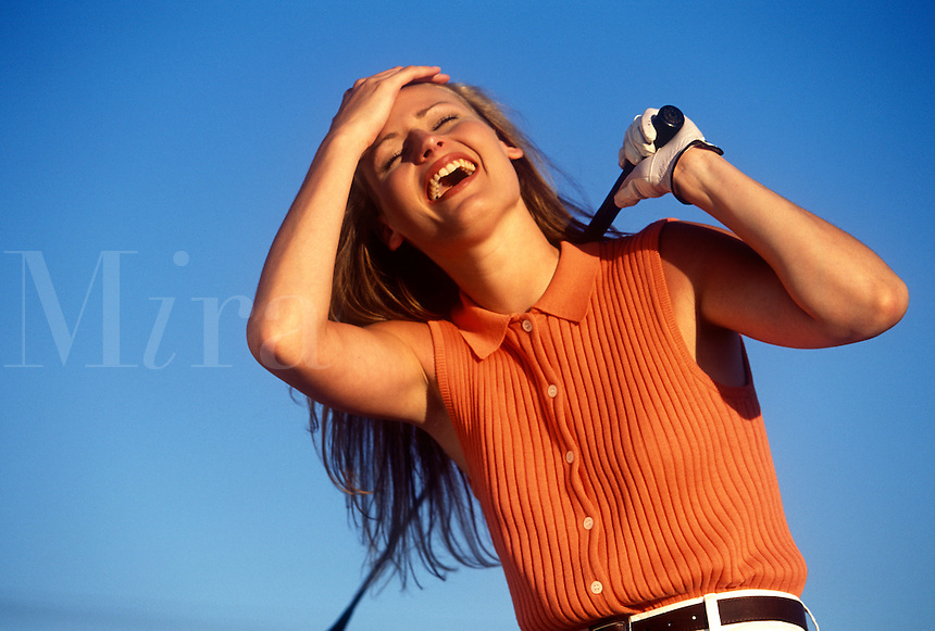 Woman golfer laughing at her tee shot.