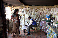 KHUTSONG, SOUTH AFRICA - OCTOBER 16: Bafana Mashata, age 17, does his home work in the family tin shack on October 16, 2012, in Khutsong, South Africa. Khutsong, a black township. is located about 56 miles west of Johannesburg, and surrounded by gold mines. Because of recent strikes many mineworkers has been fired which is making the poverty worse here.  His mother, Catherine Mashata, age 37, is unemployed. (Photo by: Per-Anders Pettersson)