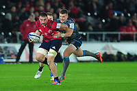 Jack O'Donoghue of Munster is tackled by Scott Williams of Ospreys during the Heineken Champions Cup Round 1 match between the Ospreys and Munster at the Liberty Stadium in Swansea, Wales, UK. Saturday 16th November 2019