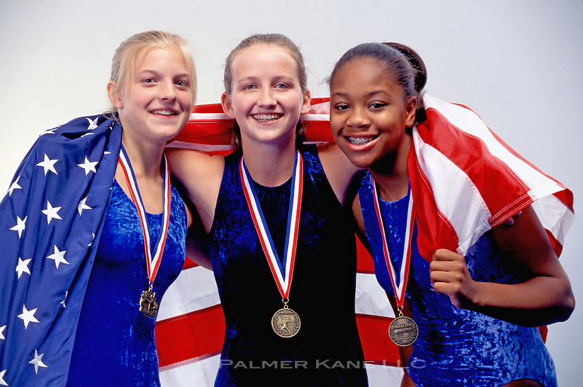 Winning Female gymnasts drape themselves in American flag