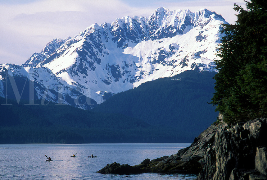 Three kayakers paddle in Berners Bay with Lions Head Mountain as a backdrop in southeast Alaska.
