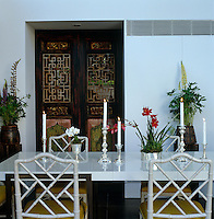 The dining room is furnished with faux-bamboo chairs, a lacquer and bronze table and ornate 19th century Chinese screens