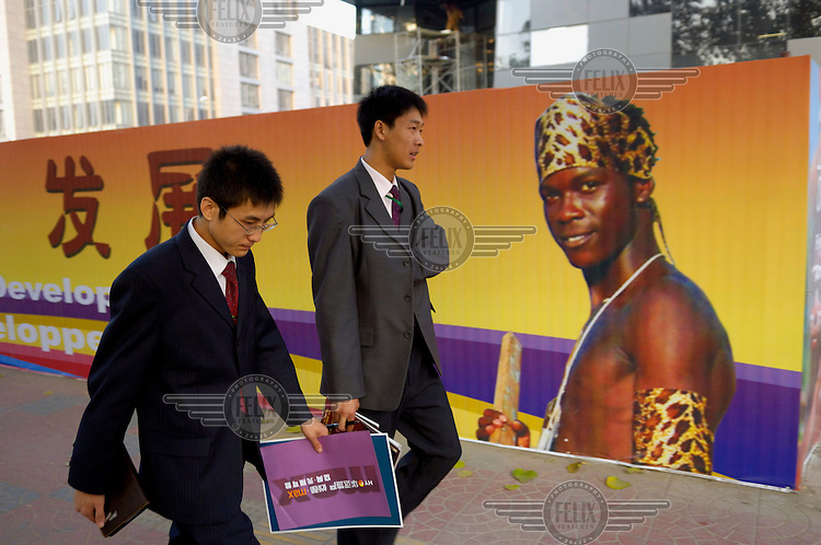 Two office workers pass a propaganda poster for the 2006 China-Africa Summit. The Summit celebrated fifty years of diplomatic relations and was intended to strengthen the political and economic ties between China and Africa.